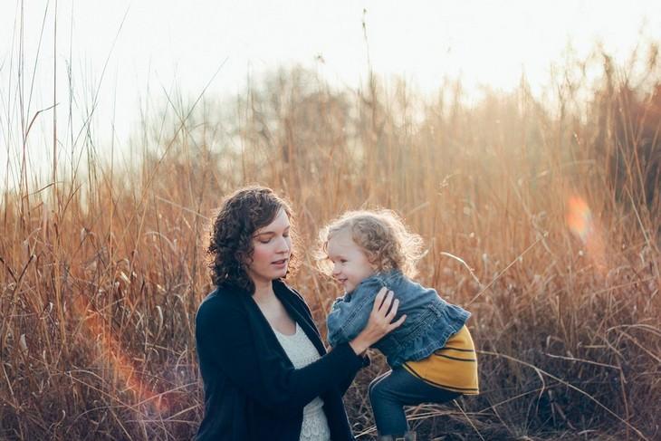 סיכום שיטת החינוך של דר ספוק: אישה מחזיקה את ילדתה בשדה