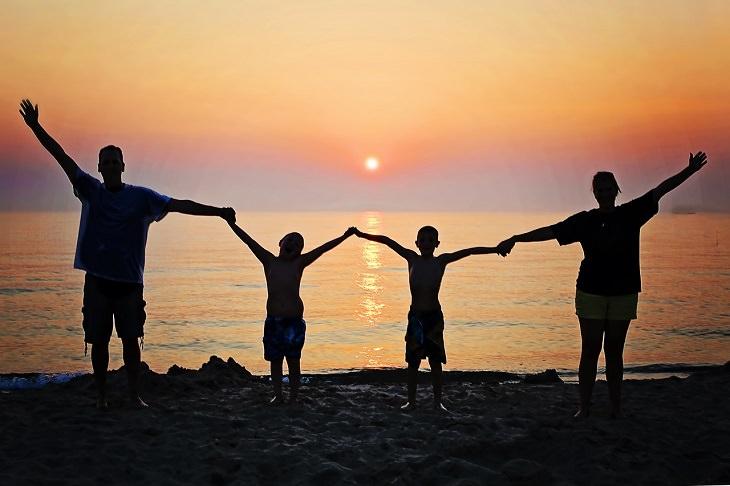 סיבות להודות להורים: משפחה אוחזת ידיים על רקע שקיעה וים