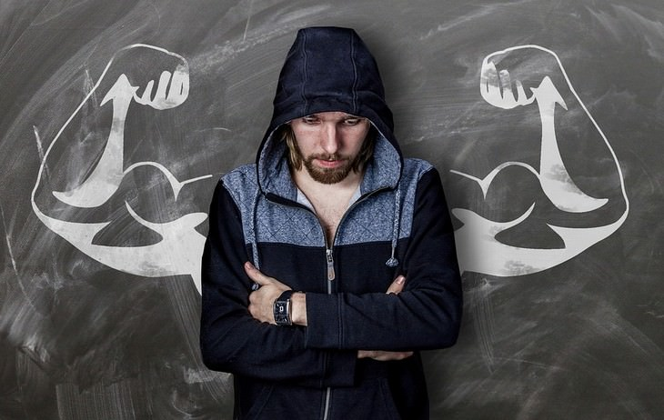 משפטים להחזרת החיים למסלול: אדם שלוב ידיים עומד בגב ללוח עם איור של ידיים שריריות עליו