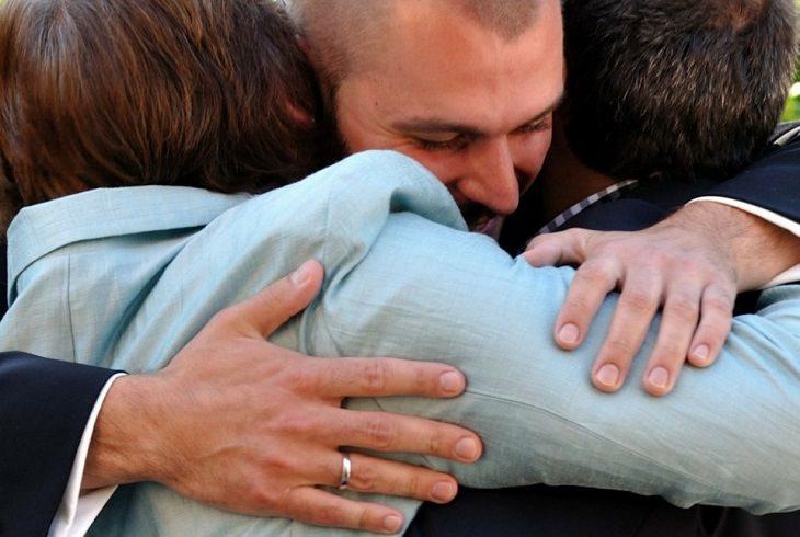 סיבות להודות להורים: בן מתחבק עם הוריו