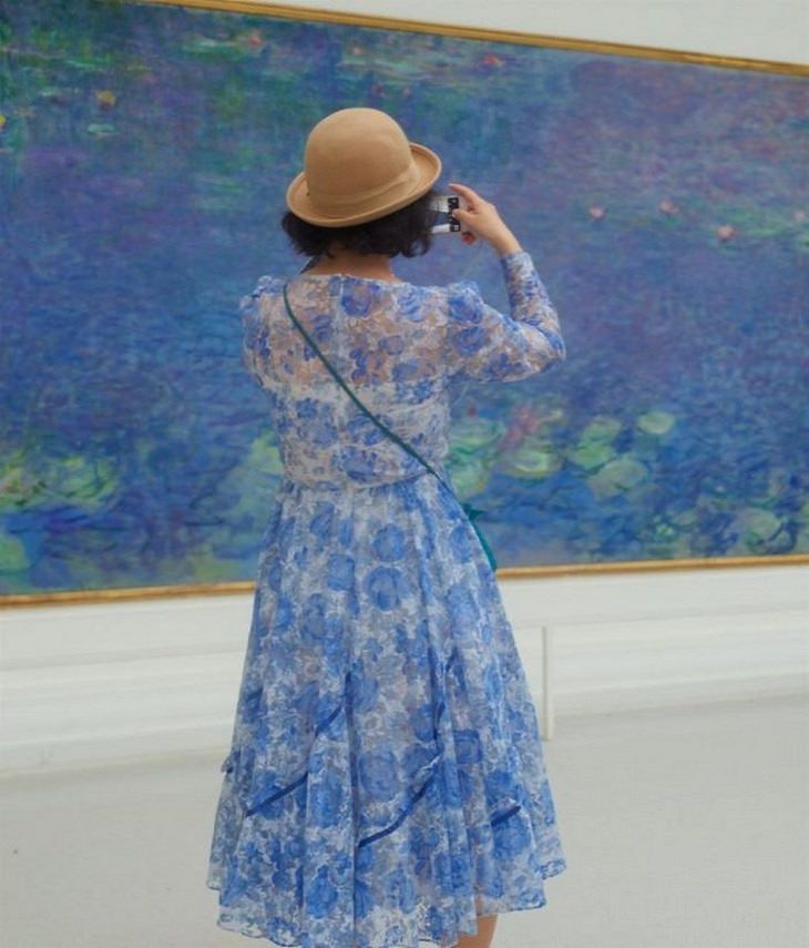 אנשים מבקרים במוזיאון שדומים לציורים שהם מסתכלים עליהם