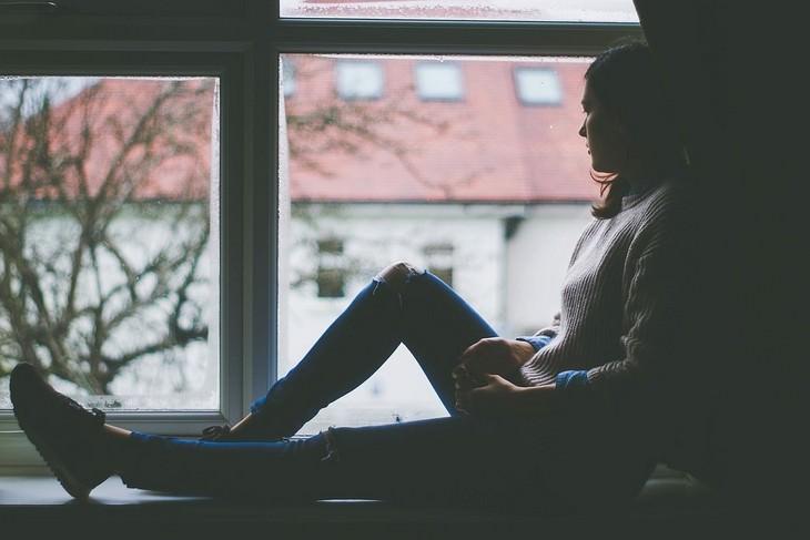 טיפים להתגברות על דיכאון בעזרת עיצוב הבית: אישה יושבת על אדן החלון ומביטה מחוצה לו
