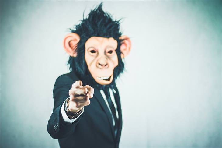 תיאוריות פסיכולוגיות שישנו לכם את החיים: אישה בחליפה עם מסכת קוף מצביע על המצלמה