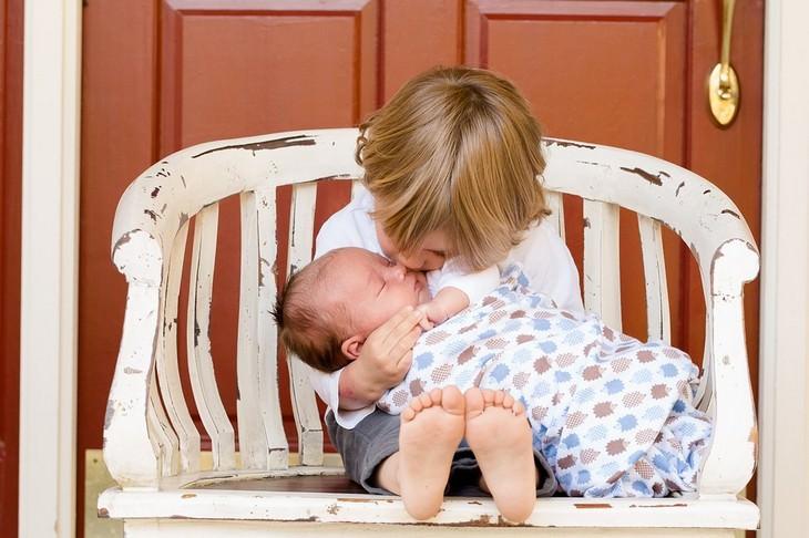 טיפים להתמודדות עם רגרסיה של ילדים: פעוט נושק לאחיו התינוק כשהם ישובים על ספסל עץ