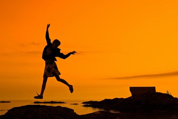 אמיתות על החיים: אישה מקפצת בין סלעים על שפת הים בשקיעה