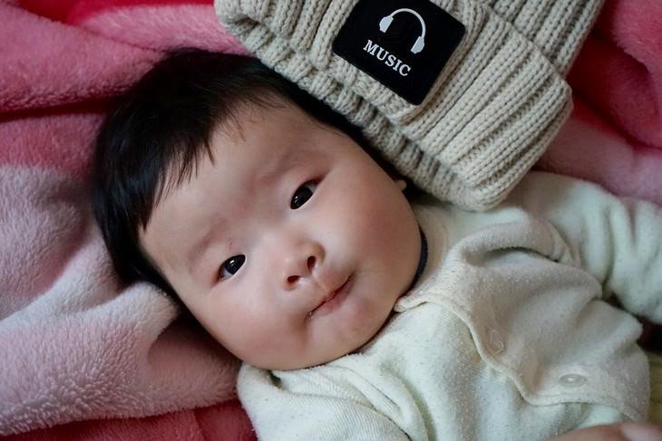 חינוך לפי פנלופה ליאך: תינוק שוכב ליד כובע עם ציור של אוזנית