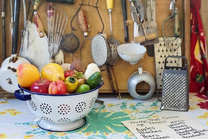 טיפים למטבח: קערת פירות לצד כלי מטבח תלויים