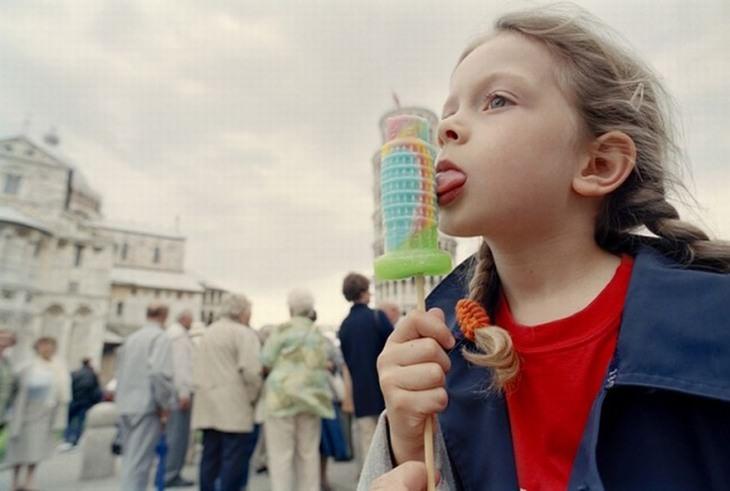 תמונות משעשעות שצריך להסתכל עליהן פעמיים: ילדה מלקקת ארטיק בצורת מגדל פיזה, בדיוק מול מגדל פיזה