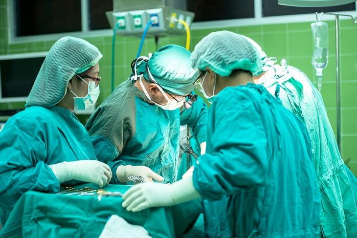 מחלות שכאבי גב מעידים עליהן: רופאים בחדר ניתוח רוכנים מעל מטופל