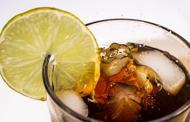 השפעות שליליות של קולה על הגוף: כוס של קולה עם פרוסת לימון על השוליים