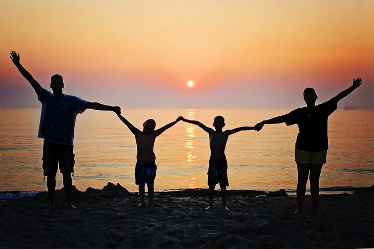 סודות של משפחות מאושרות: משפחה אוחזת ידיים ומניפה אותן מעלה מול ים בשקיעה