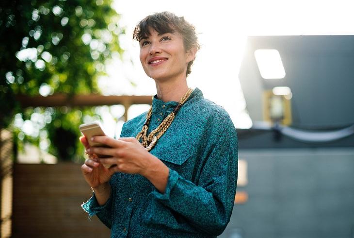 כך תהפכו לאנשים שלא ניתן לעמוד בפניהם: אישה עומדת עם הטלפון הנייד בידה ומסתכלת לאופק