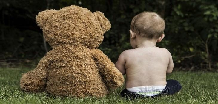 סימנים לכך שתינוקות אוהבים אתכם: תינוק יושב על דשא ליד בובת דובי גדולה
