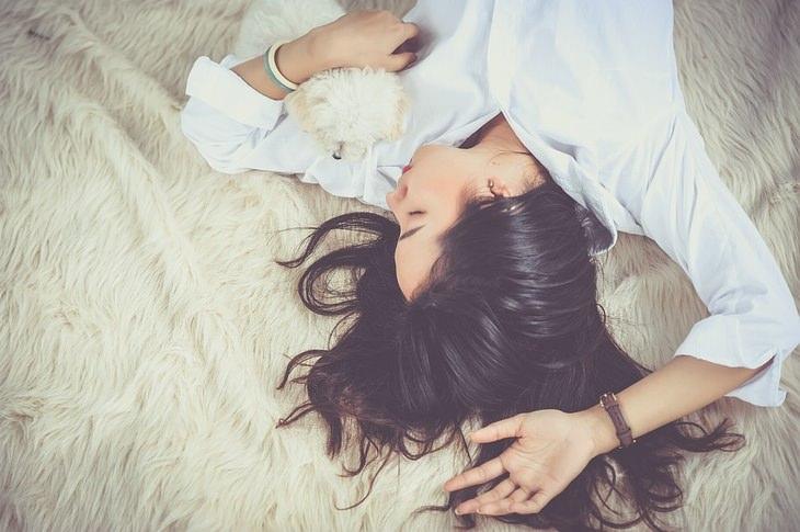 נזק של שינה עם שיער רטוב ומניעתו: אישה ישנה במיטה עם כלב קטן