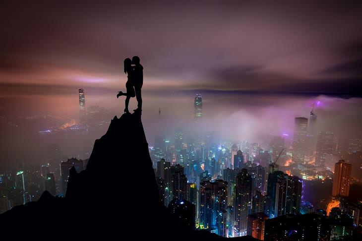ארבעת סוגי האוהבים: צללית של זוג עומד על צוק מול נוף עירוני בשעת ערב