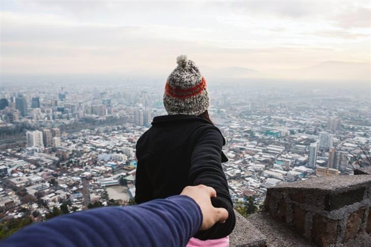 ארבעת סוגי האוהבים: אישה מובילה גבר יד ביד מול נוף עירוני