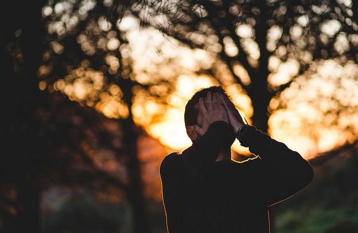 השפעתן של תלונות על המוח: איש מכסה את פניו ביער