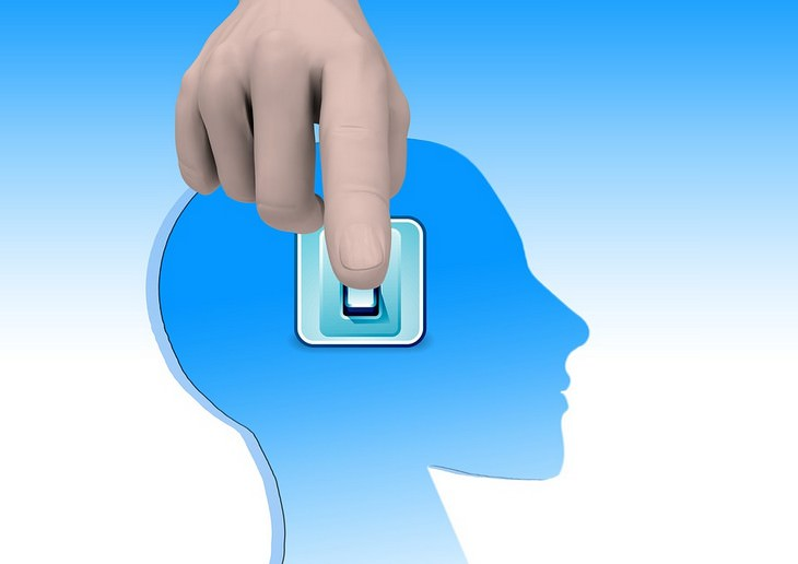 השפעתן של תלונות על המוח: איור של יד לוחצת על מתג שנמצא על ראש