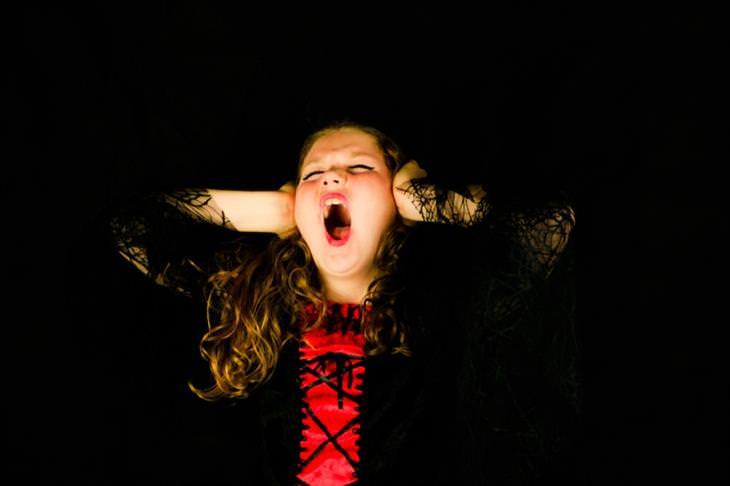 סימנים לדלקת קרום המוח אצל ילדים: ילדה אוטמת את אוזניה וצועקת