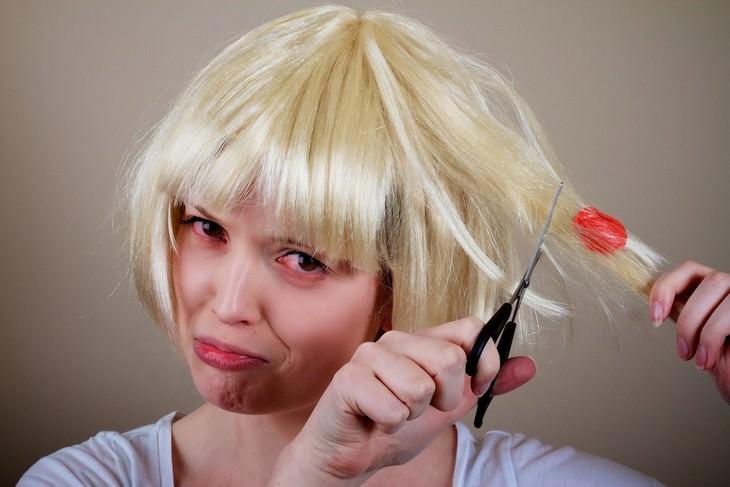 שיטות להסרת מסטיק משיער: אישה מחזיקה מספריים ועומדת לגזור מחלפת שיער שדבוק אליה מסטיק