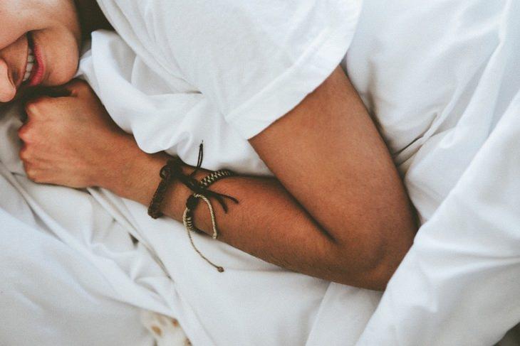 תרסיסים משמנים אתריים: בחור צעיר מתכרבל בין סדיני המיטה
