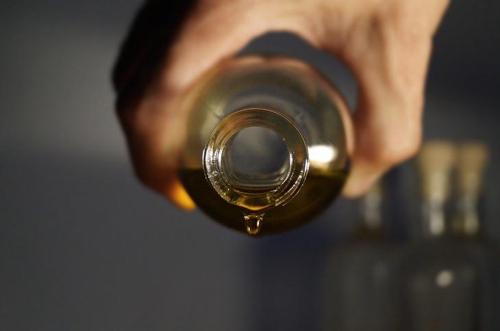 תרסיסים משמנים אתריים: יד מוזגת שמן מתוך בקבוק