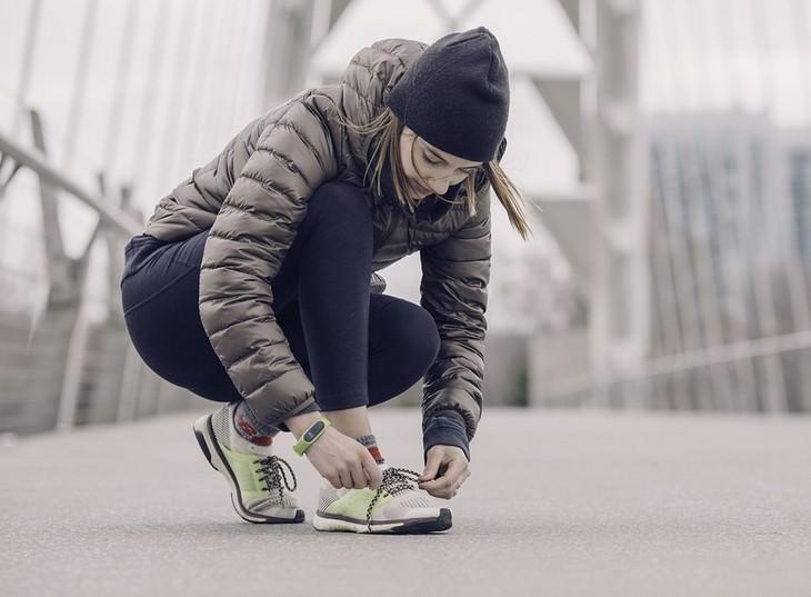 טריקים מגובים מדעית להגברת הביטחון העצמי: אישה לבושה בביגוד חם שורכת שרוכים של נעלי ספורט על גשר