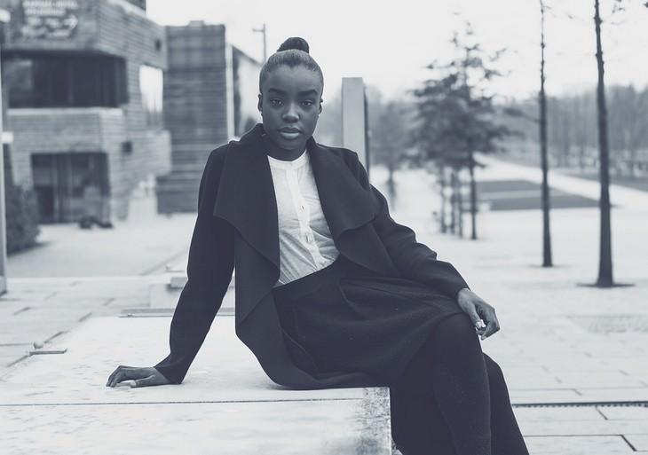 טריקים מגובים מדעית להגברת הביטחון העצמי: אישה יושבת על מדרגה ומישירה מבט עם המצלמה