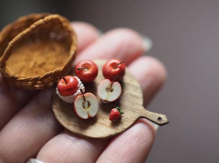 יצירות מיניאטוריות מפורטות: יד אוחז בקרש חיתוך קטן שעליו תפוחים וחצאי תפוחים
