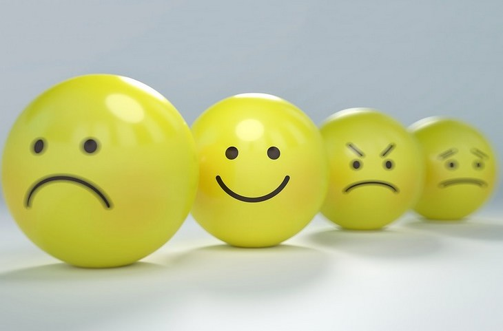 טריקים מגובים מדעית להגברת הביטחון העצמי: כדורים עם פרצוף זועף שביניהם כדור עם פרצוף מחויך