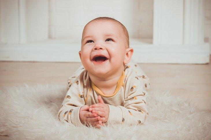 הסיבות להתנהגויות מוזרות של תינוקות: ילד שוכב על בטנו על השטיח ומחייך