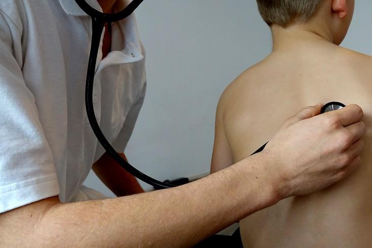 דברים שרופא הילדים שלכם לא מגלה לכם: רופא בודק ריאות של ילד עם סטתוסקופ