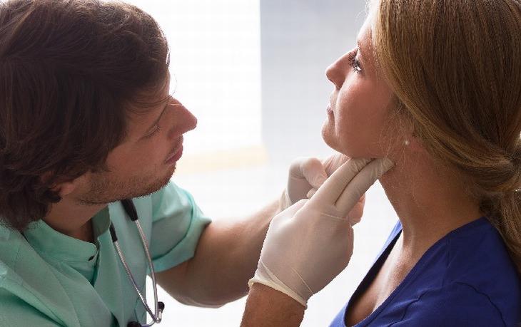 מאכלים שיקלו על כאב הגרון שלכם: רופא בודק גרון של אישה