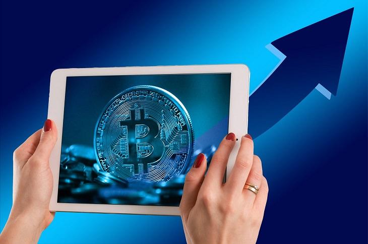 הסבר מהו הביטקוין: אישה מחזיקה מחשב לוח שעליו סמל מטבע הביטקוין