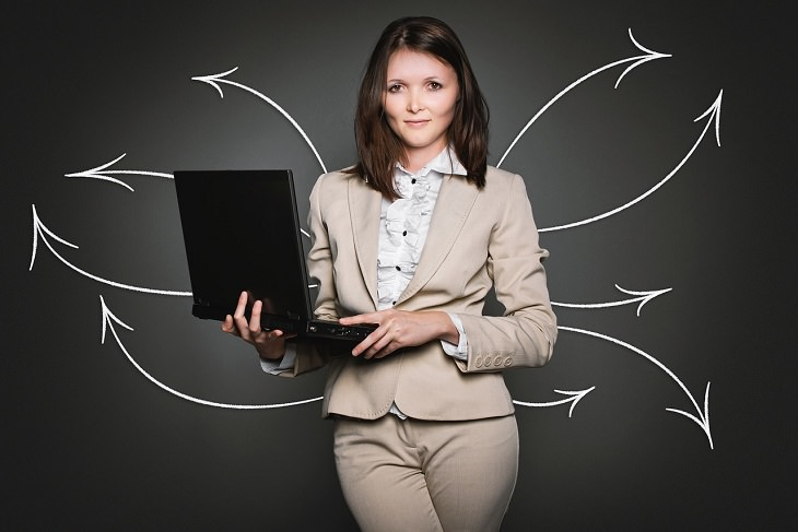 סימנים לכך שאתם בעלי חוסן מנטלי: אישה אוחזת מחשב נייד ומאחוריה איורים של חצים לכיוונים שונים