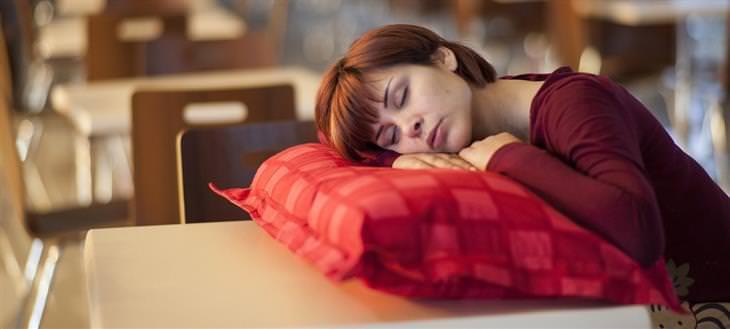 טעויות שמונעים מכם שינה ערבה: אישה משיכה את הראש על כרית שעל שולחן