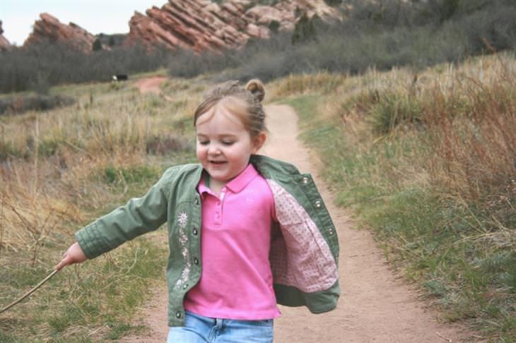 האזהרה הכללית שהורים חייבים להפסיק להגיד לילדים: ילדה רצה בשביל בטבע עם מקל בידה