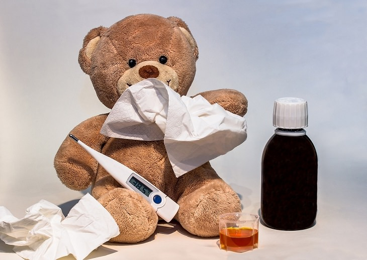 מחלות מתחפשות: בובה של דוב עם בקבוק של תרופה, ממחטת נייר ומדחום לידו