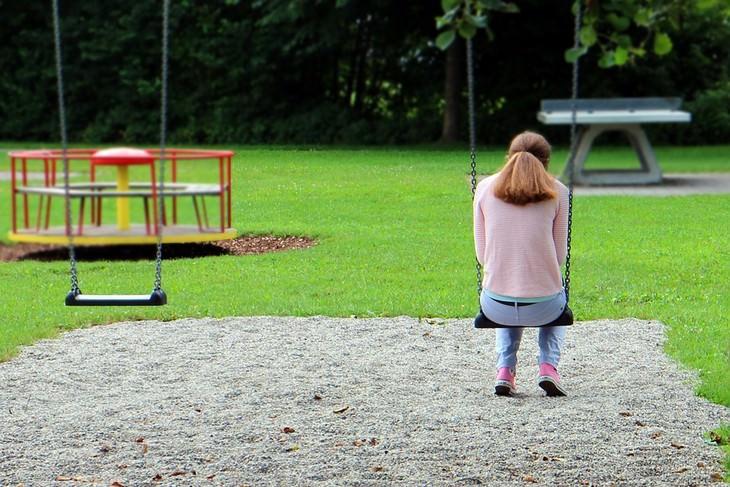 סימנים להפרעות קשב וריכוז אצל בנות: צילום אחורי של ילדה יושבת על נדנדה