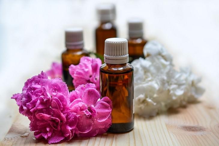 שמנים אתרים לטיפול בכאבי ראש: בקבוקים של שמנים אתריים ליד פרחים