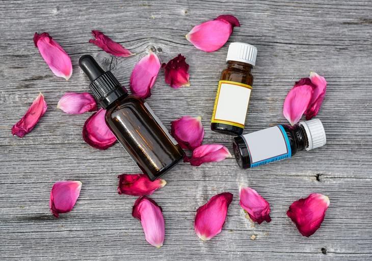 שמנים אתרים לטיפול בכאבי ראש: בקבוקים של שמנים אתריים ליד עלי כותרת