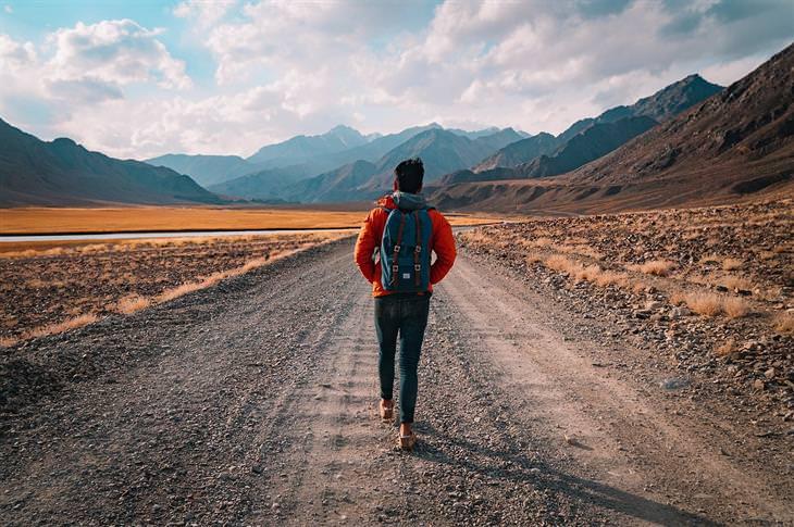 אשליות בחיים: איש הולך בשביל ישר וארוך עם תיק על הגב