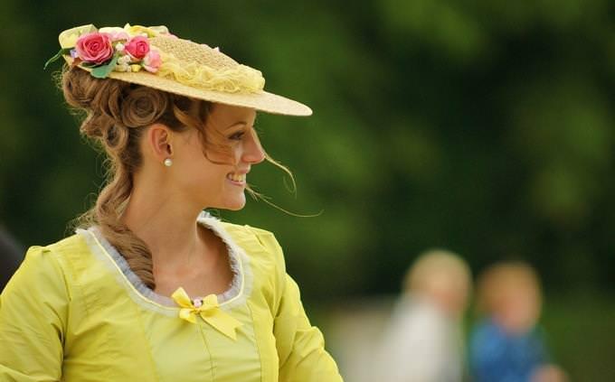 מבחן טריוויה ביטויים ופתגמים: אישה לבושה בשמלה וכובע תקופתיים