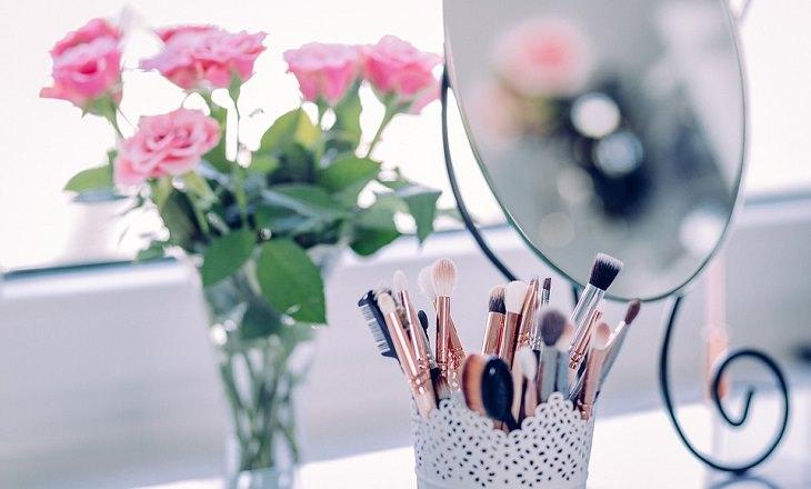 המדריך לבוקר המושלם: מוצרי איפור ליד מראה וזר פרחים