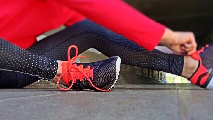תרגיל גוף כוללני: אישה שורכת נעלי ספורט על הרצפה