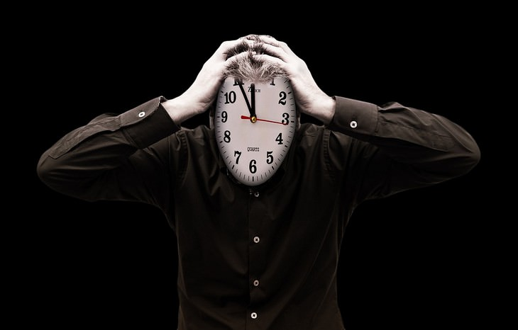 סיבות ופתרונות להתעוררות באמצע הלילה: איש עם שעון במקום פנים אוחז בראשו