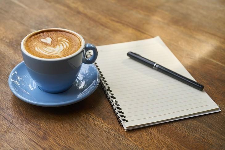 איך לחשוב חיובי בכל יום: כוס קפה מונחת ליד מחברת שעליה עט