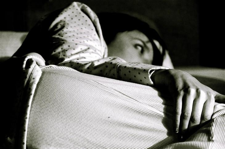 סיבות ופתרונות להתעוררות באמצע הלילה: אישה ערה במיטה