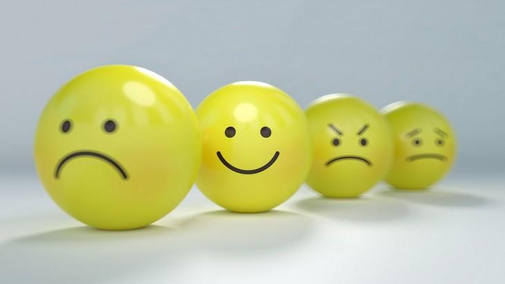 איך לחשוב חיובי בכל יום: שורה של עיגולי סמיילי עם חיוך זעוף שביניהם סמיילי מחויך