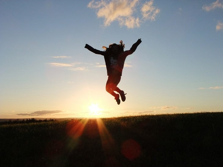 איך לחשוב חיובי בכל יום: אישה קופצת מעלה מול השקיעה